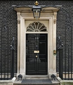10 Downing Street door by Jdforrester crop from original by Prime Minister's Office, HM Government. (2010 Official Downing Street pic.jpg) [OGL (http://www.nationalarchives.gov.uk/doc/open-government-licence/version/1/)], via Wikimedia Commons