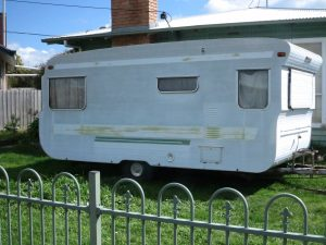 Old caravan outside a house